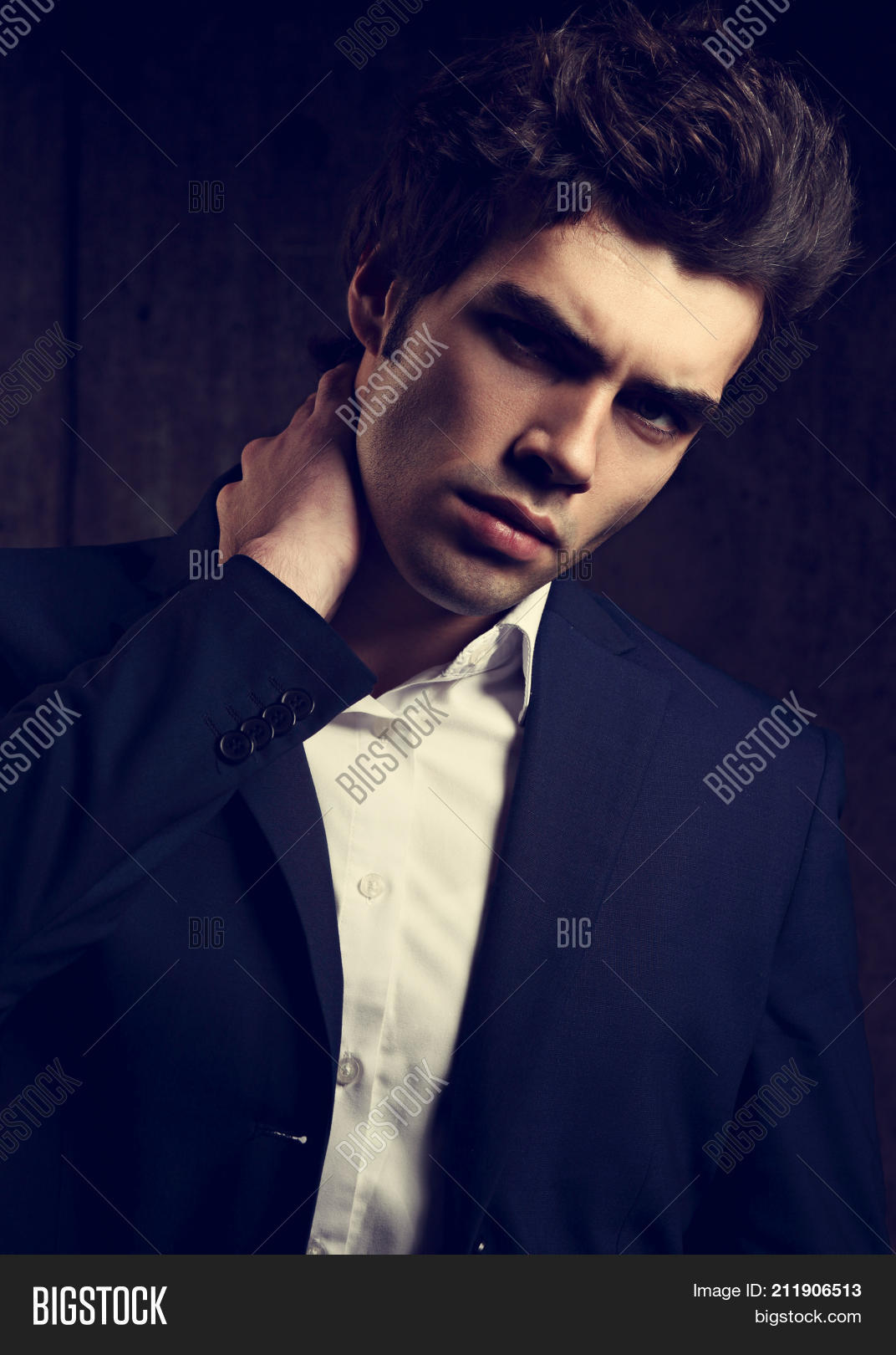 eb409798 Charismatic handsome business man posing in blue fashion suit and white  style shirt looking on dark shadow background. Closeup toned color portrait