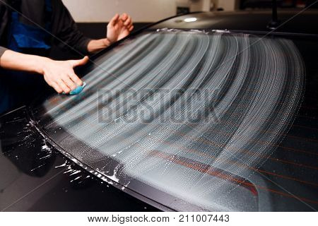 Master installs a tint film for the car glass with a hairdryer and spatula with glare of light. Concept tinting car