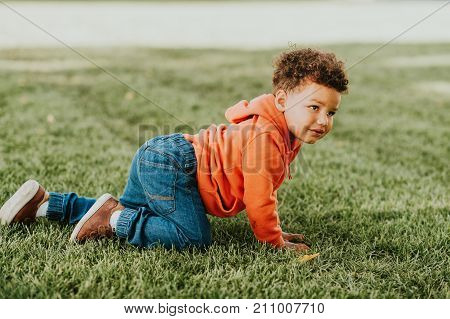 Adorable funny toddler playing outside baby boy enjoying nice sunny day 1-2 year old african kid crawling on the grass film look toned image