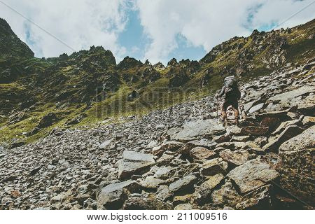Adventurer man climbing in mountains with backpack Travel Lifestyle hiking concept summer vacations outdoor getaway exploring