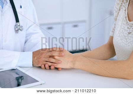 Doctor reassuring his female patient by touching her hands while talking. Symbol of support and trust in medicine.