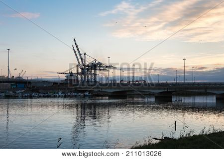 Container Terminal, Shipyard and Cranes at Sunset and Their Reflection
