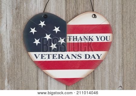 Thank You Veterans Day message on a retro USA flag on a heart shape wood sign on weathered wood