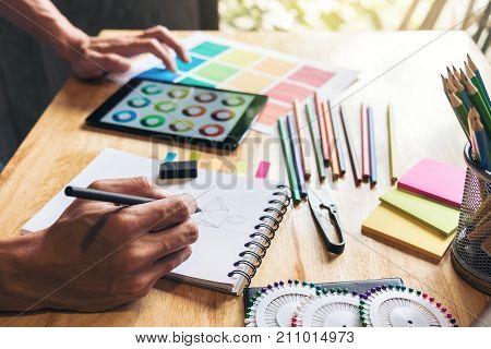 Fashion Designer Stylish Concept Young dressmaker or designer drawing design sketch working for clothes and Choose color bar in digital tablet in manufacturing office studio.