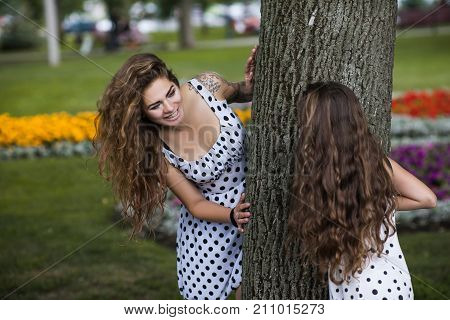 Family hide-and-seek. Active leisure time in park. Stylish youth lifestyle, nature background. Forever young, summer happiness