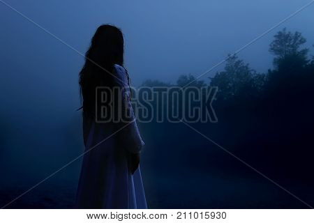 Mysterious Woman in White Dress in Misty Forest