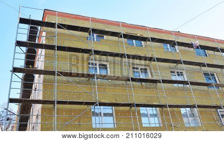 Solid wall insulation with rock wool. Energy efficiency house wall renovation for energy saving. Exterior house wall heat insulation with mineral wool. External wall insulation.