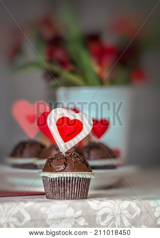 Chocolate cupcakes decorated with red hearts on a plate on a table with flowers on the background