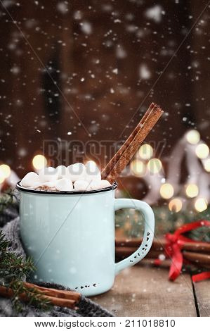 Enamel cup of hot cocoa with mini marshmallows and cinnamon bark. Pine boughs and gray scarf against a rustic background with beautiful Christmas lights of bokeh with falling Snow.