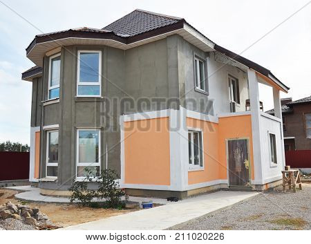 House renovation and repair with new stucco plastering and painting wall. Painting house walls.