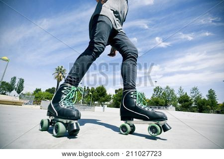 a young caucasian man roller skating with quad skates in an outdoors skate park