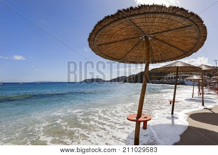 High tide on Agia Pelagia beach on Crete in Greece with manipulated parasol