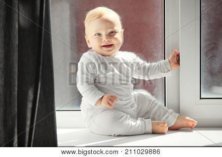 Playful baby with blond hair and grey eyes in white crawlers sits on windowsill full of light that comes from window covered with winter frost.