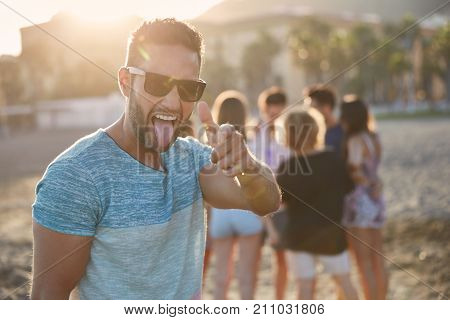 Happy Man Standing On Beach With His Friends Pointing At Camera