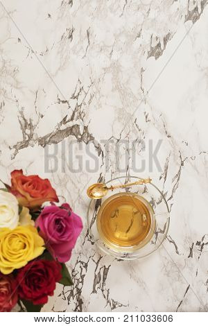 A Glass Cup Of Tea. Beautiful Fresh Flowers On Light Marble Table, Top View. Colorful Bouquet Of Ros