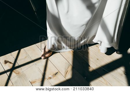 Bride Putting On Wedding Shoe. Artwork. Close-up