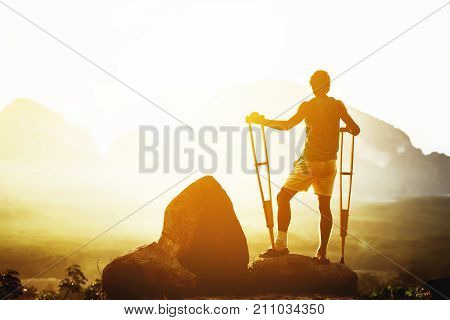Disabled man stands with crutches on background of mountains at sunrise or sunset. Space for text