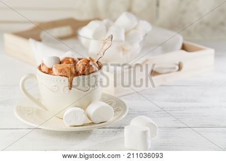 Hot cocoa with marshmallow on white table