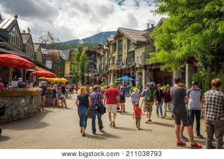 WHISTLER, BRITISH COLUMBIA, CANADA - JULY 2, 2017 : Scenic street view with many tourists  in Whistler Village. Whistler is a canadian resort town visited by over 2 million people annually.
