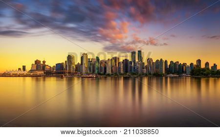 Sunset skyline of Vancouver downtown as seen from Stanley Park, British Columbia, Canada . Long exposure.