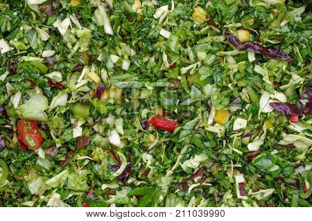 Chopped fresh vegetables prepared as fresh pet food for parrots the basis of chop. Includes sweet peppers red cabbage dark leafy greens mangetout peas pak choy celery and sweet corn.