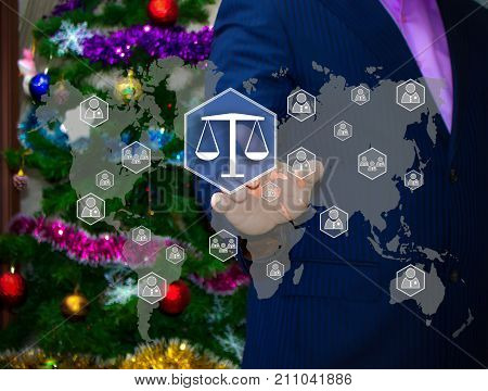 The Businessman Chooses Libra  On The Touch Screen, The Backdrop Of The Christmas Tree And Decoratio