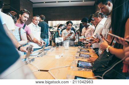 PARIS FRANCE - SEP 20 2014: Apple Store interior with crowd of customers trying the latest iPhone smartphone specs during launch day