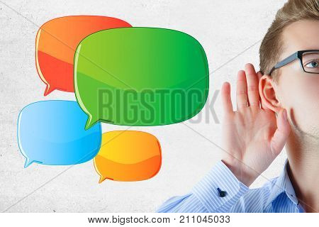 Young businessman listening carefull on concrete wall background with empty speech bubbles. Commuication concept. Mock up
