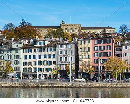 Zurich, Switzerland - 25 October, 2017: old town buildings along the Limmat river, building of the Swiss Federal Institute of Technology in Zurich above them. Zurich is the largest city in Switzerland and the capital of the Swiss canton of Zurich.