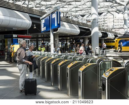 The Hague The Netherlands - August 6 2017: Two travellers at the central station The Hague at the OV check points and the platforms with trains.