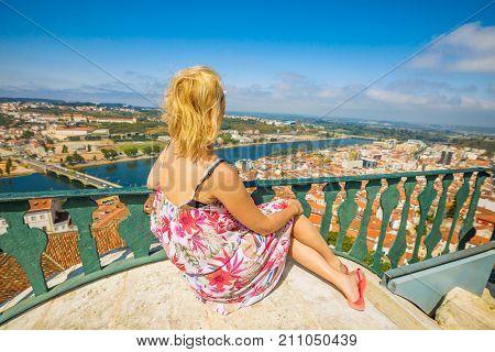 Coimbra cityscape and Santa Clara Bridge on Mondego river. Caucasian tourist woman admiring Coimbra panorama sitting on top of bell Clock Tower. Female tourist enjoys in Portugal, Europe.