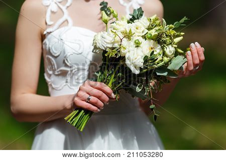 Elegant bride in a white wedding dress with lace holding in hands delicate trendy bridal bouquet of flowers in white and green colors