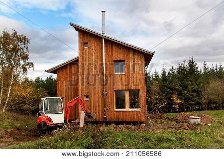 Mini excavator on construction site. Excavator regulates the terrain around the house.