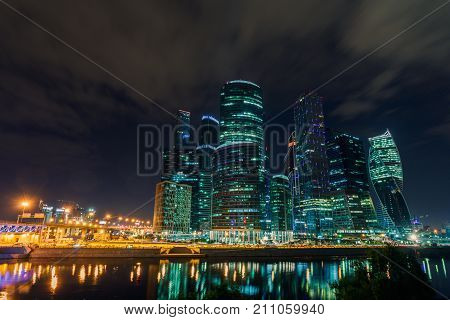 Skyscraper and transport metropolis, traffic and blurry lights of cars on multi-lane highways and road junction at night in Moscow