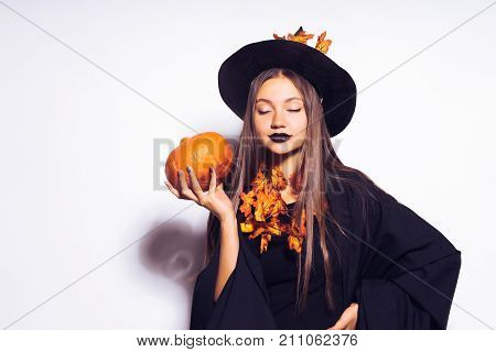a young sexy cheerful gothic girl celebrates halloween, dressed in a witch, in a big black hat, holds a pumpkin in her hands