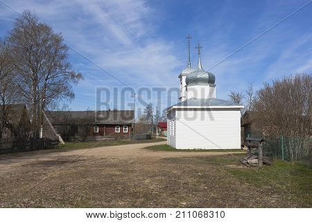 Landscape streets of the northern village in the spring. Chapel of the Assumption of the Blessed Virgin Mary in the village of Mokievskaya, Verkhovazhsky district, Vologda region, Russia