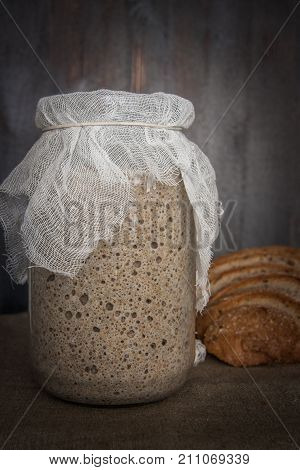 A lovely well-sourdened sourdough in a glass jar and slices of bread arranged side by side.