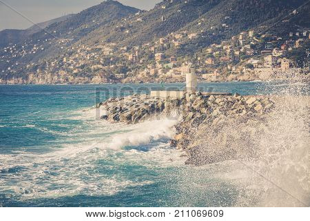 Sea, waves and lighthouse of Camogli, in the Ligurian sea in Italy. Natural landscape, mountains in the distance.