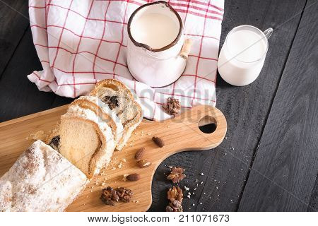 Above view over a rustic breakfast with fresh milk and a pound cake sliced on a wooden trencher covered with powdered sugar surrounded by roasted nuts.