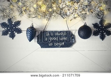 Black Chirstmas Plate With English Quote It Is Always A Good Time To Begin. Fir Branch With Fairy Lights On Wooden Background. Black Christmas Decoration Like Balls And Snowflakes.