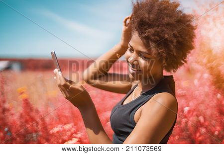 Beautiful cheerful young African American female is fixing her curly hair using frontal camera of cell phone as a mirror; vivid red colors in defocused background shallow depth of field