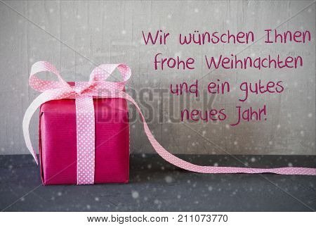 Gray Grungy Cement Wall With German Wir Wuenschen Frohe Weihnachten Und Ein Gutes Neues Jahr Means We Wish You A Meryy Christmas And A Happy New Year. Pink Gift Or Present With Bow And Snowflakes.