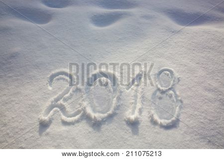 New years date 2018 written in fresh powder snow. New Year 2018 greeting, 2018 numbers written on snow field, greeting card background.