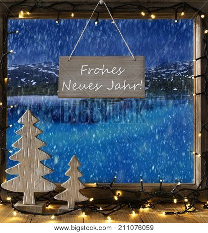 Sign With German Text Frohes Neues Jahr Means Happy New Year. Window Frame With Winter Landscape With Snow. View To Snowy Mountains And Lake Or River Outside With Snowflakes. Christmas Tree And Fairy Lights.