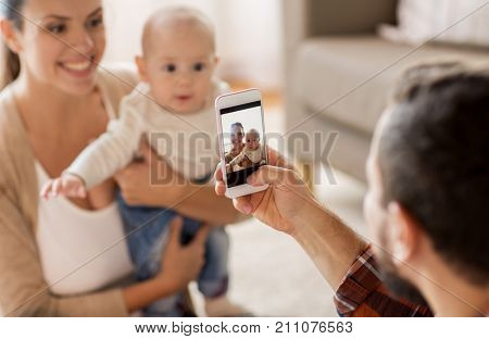 family, parenthood and people concept - happy father with smartphone taking picture of mother with baby at home