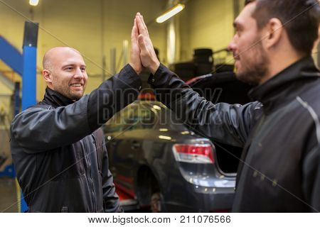 auto service, repair, maintenance and people concept - mechanics or tire changers making high five at car shop