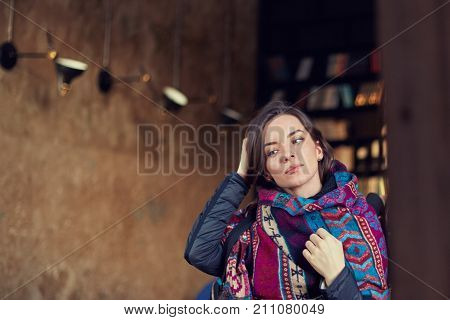 Close up shot of beautiful mixed race young brunette woman looking at the mirror touching hair leaving modern cafe dressing up by the exit. Attractive female student dressed in authentic scarf indoor.