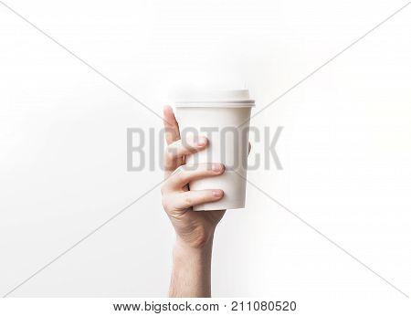 Hand holding a mug Paper Coffee Cup with delicious coffee in a cafe on a white background mock up blank your cafe shop design