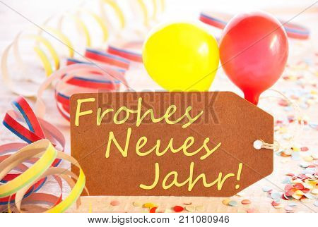 One Label With German Text Frohes Neues Means Happy New Year. Party Decoration Like Streamer, Confetti And Balloons. Wooden Background With Vintage, Retro Or Rustic Syle