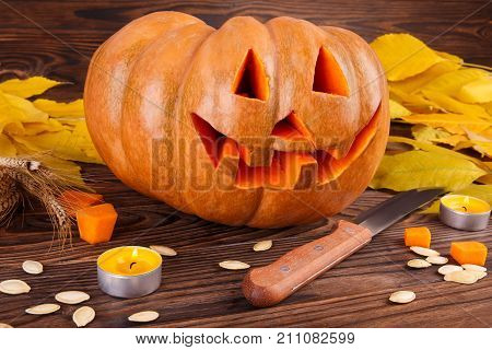 Tasty orange pumpkin on a wooden background. Pieces of a pumpkin with seeds and leaves. Close-up of pumpkin. Halloween concept.